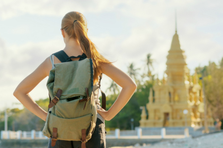 Young woman looking at golden pagoda. Hiking at Asia.